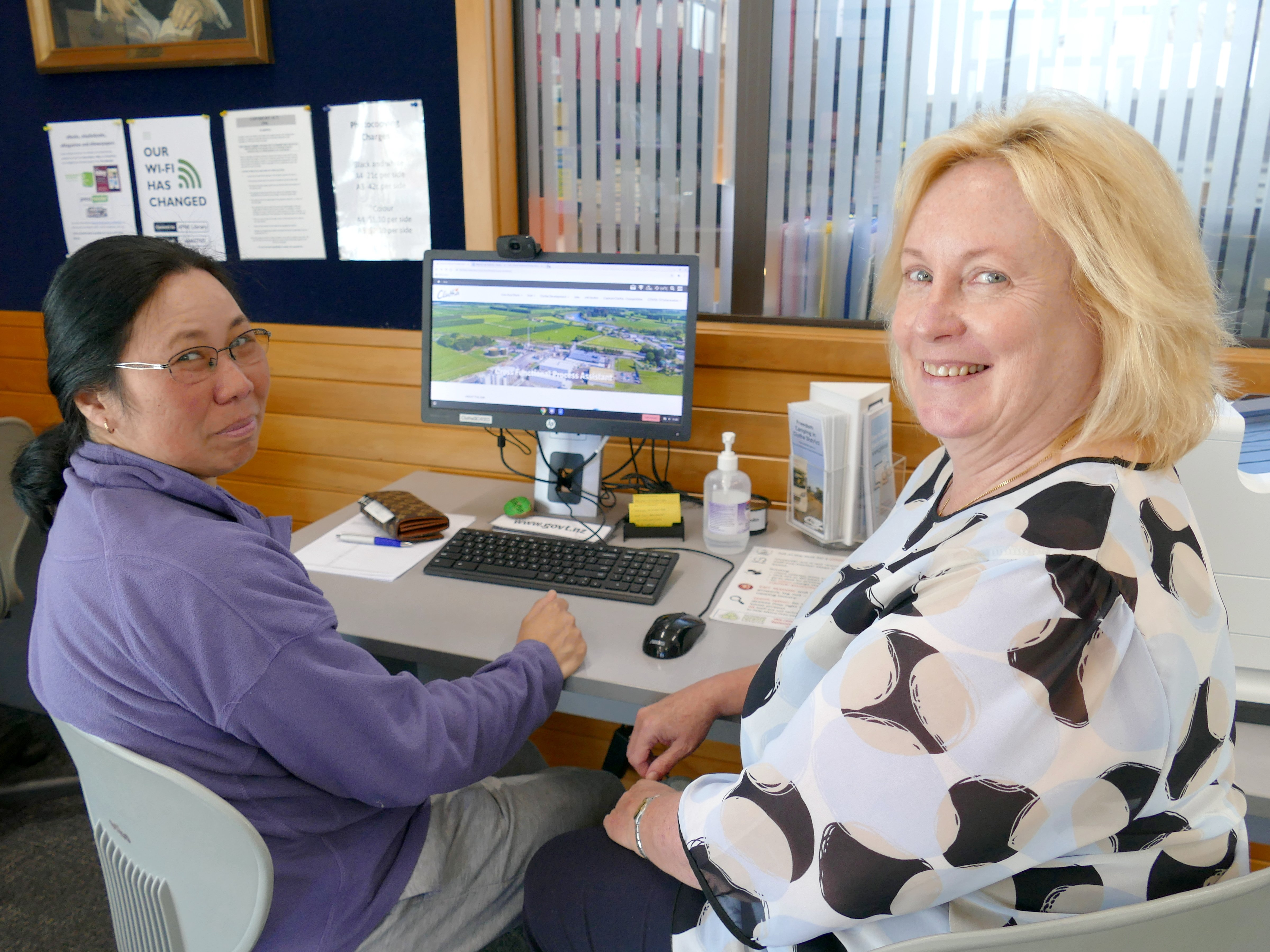 Balclutha resident Faye Ocampo (left) uses the town's free library internet service to look for...