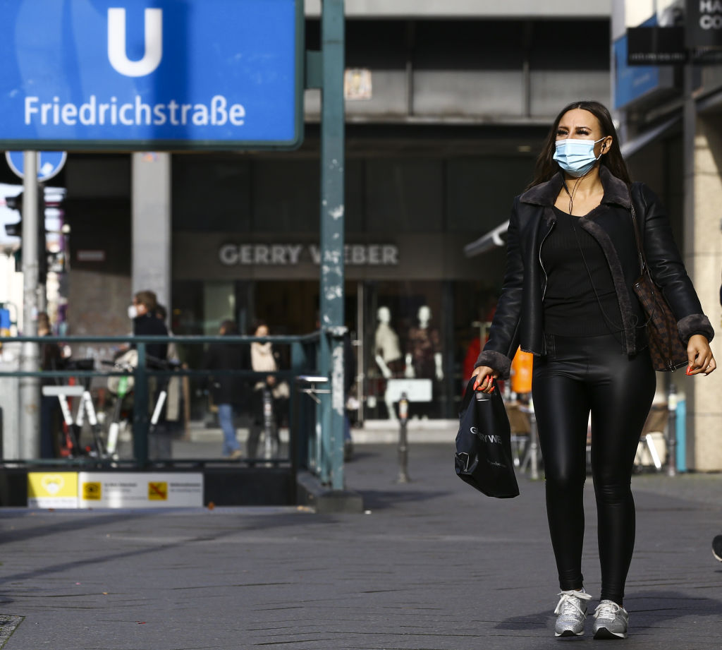 A masked woman walks along a street in Berlin. Photo: Getty Images