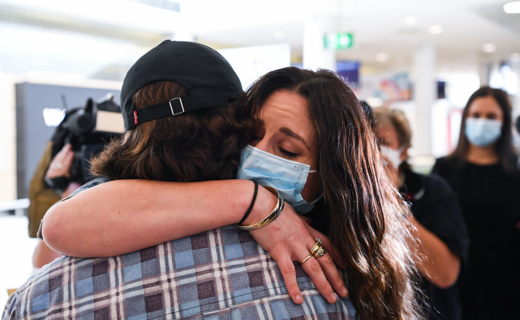 A woman hugs her loved one after arriving in Sydney on the first flight. Photo: Getty