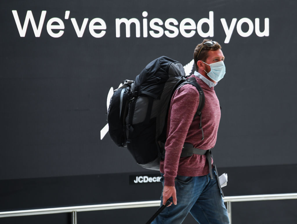 A passenger wearing a facemask walks through the airport's international arrivals area. Photo: Getty