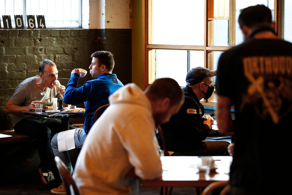 People dine in a cafe in Melbourne, where lockdown conditions have been lifted. Photo: Getty