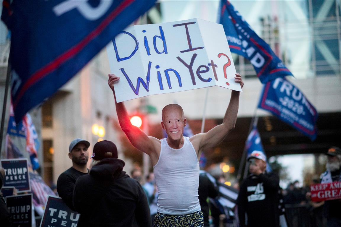 A Trump supporter carries a sign while wearing a Joe Biden mask during a protest outside of the