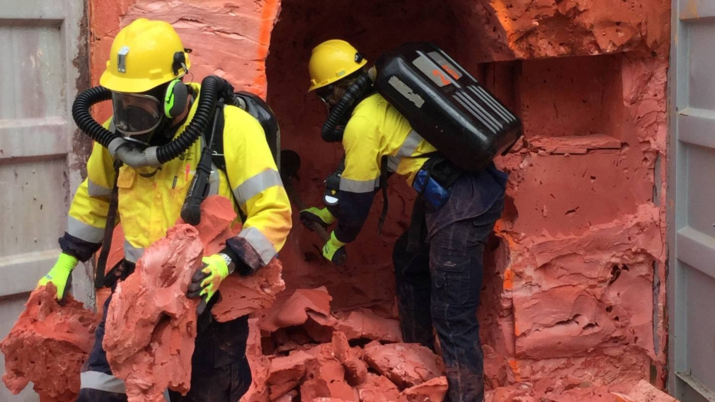Miners practice tunneling through a shipping container filled with the same foam as the Rocsil...