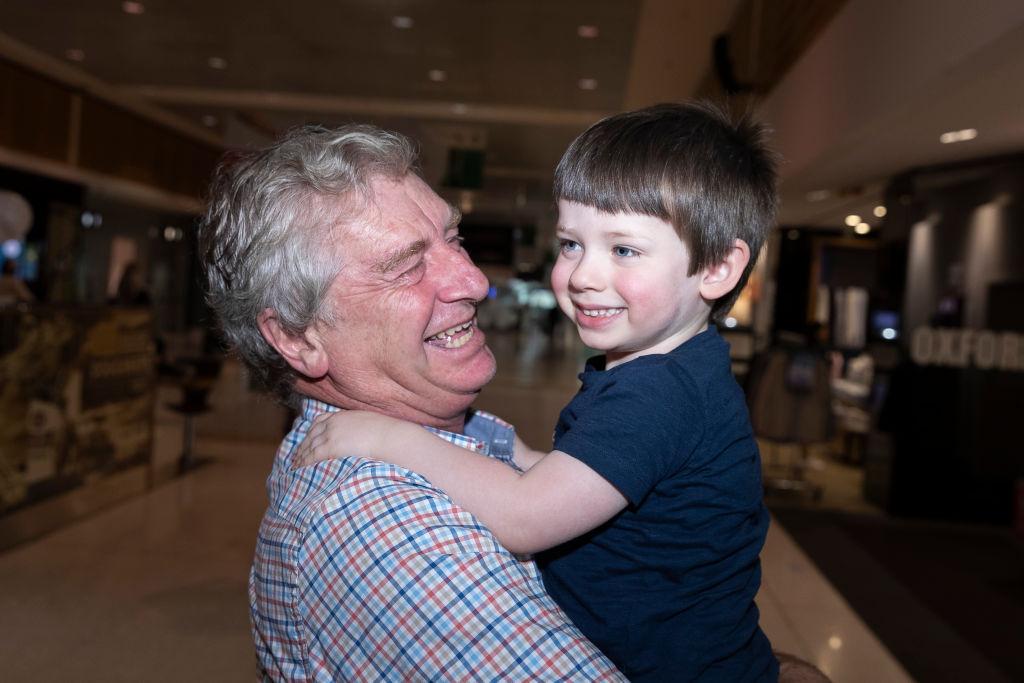 Sydney grandad Alan Kinkade hugs his grandson Tom, who lives in Melbourne, upon meeting at Sydney...