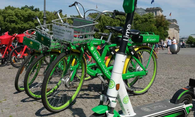 An electric scooter from bike and scooter sharing company Lime stands near sharing bicycles. Photo: Getty Images