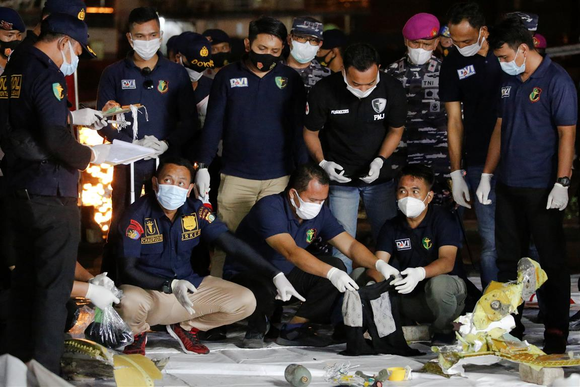 Disaster Victim Identification officers at Jakarta's Tanjung Priok port look through items found...