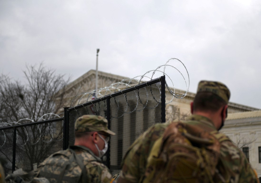 Officers from the National Guard walk near a fence lined with barbed wire at the Capitol grounds...