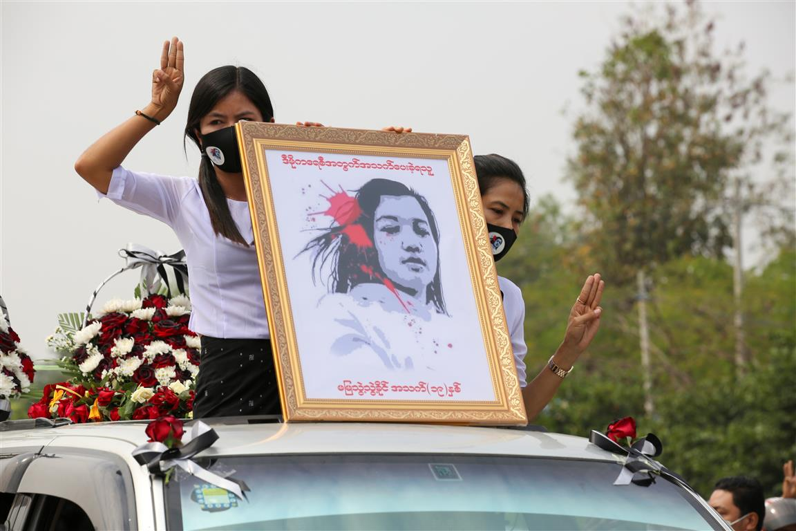 Women hold a portrait of Mya Thwate Thwate Khaing, a young protester who was killed during...