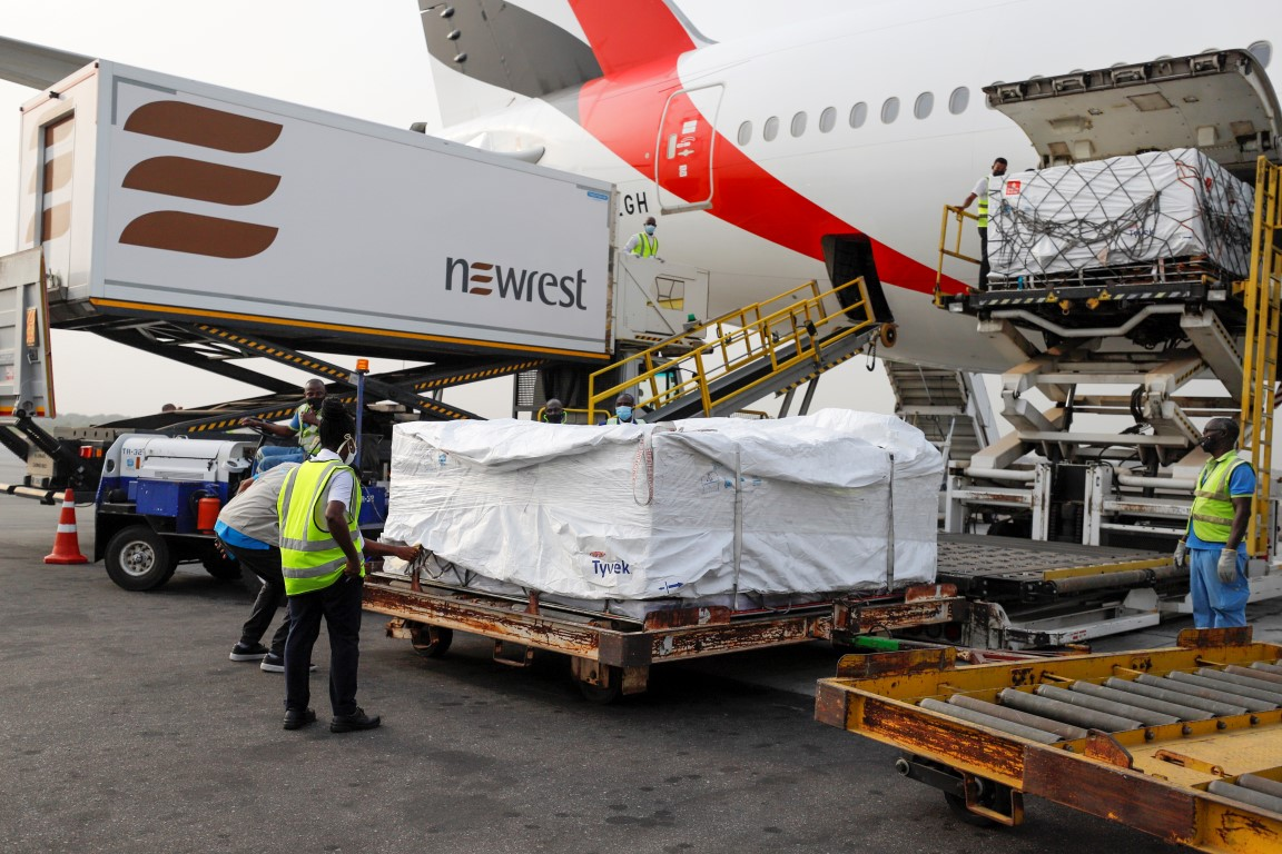 Workers offload boxes of AstraZeneca/Oxford vaccines under the Covax scheme, at the airtport in...