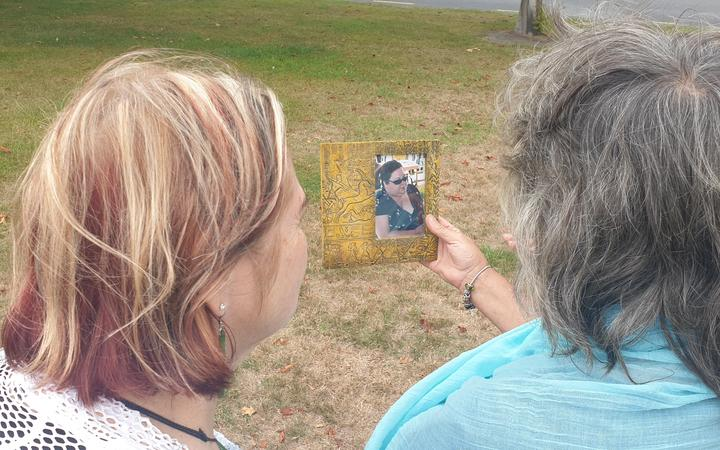 Two colleagues hold a photo of Nina Bishop. Photo: RNZ / Eleisha Foon