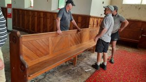 Volunteers discuss how to get an extra large pew out of the church in preparation for the...