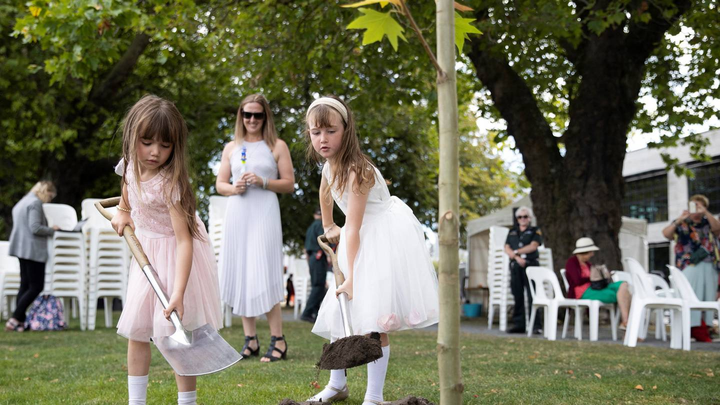 Breanna Gowland watching her daughters plant a memorial tree in Christchurch yesterday. Photo:...
