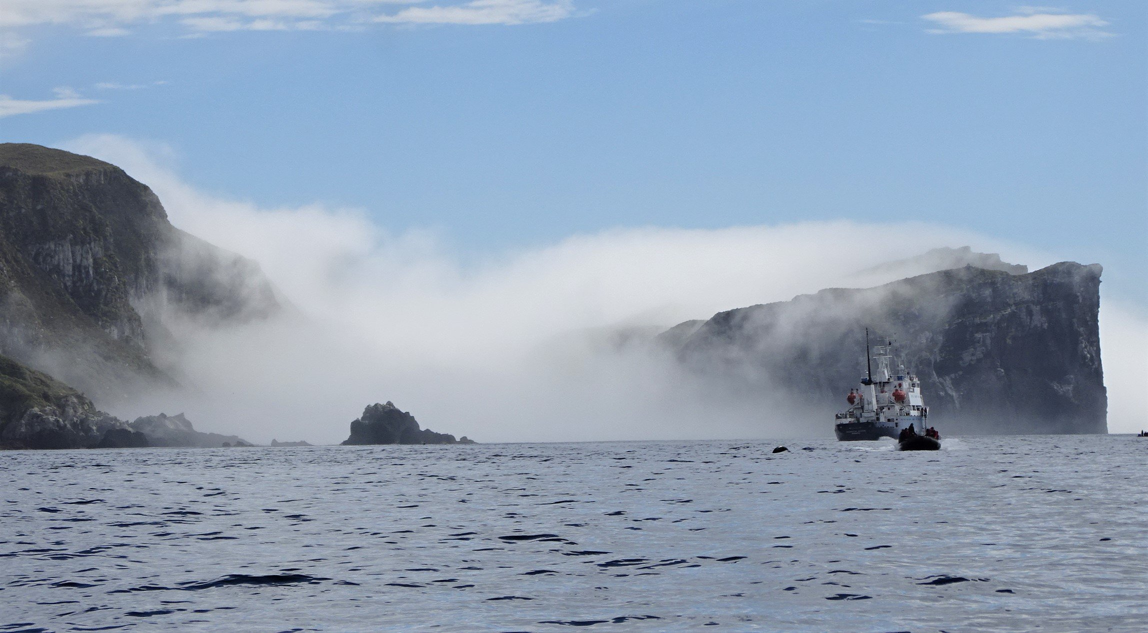 The Antipodes Islands emerge from a sea fog and The Spirit of Enderby  anchored in its waters. ...