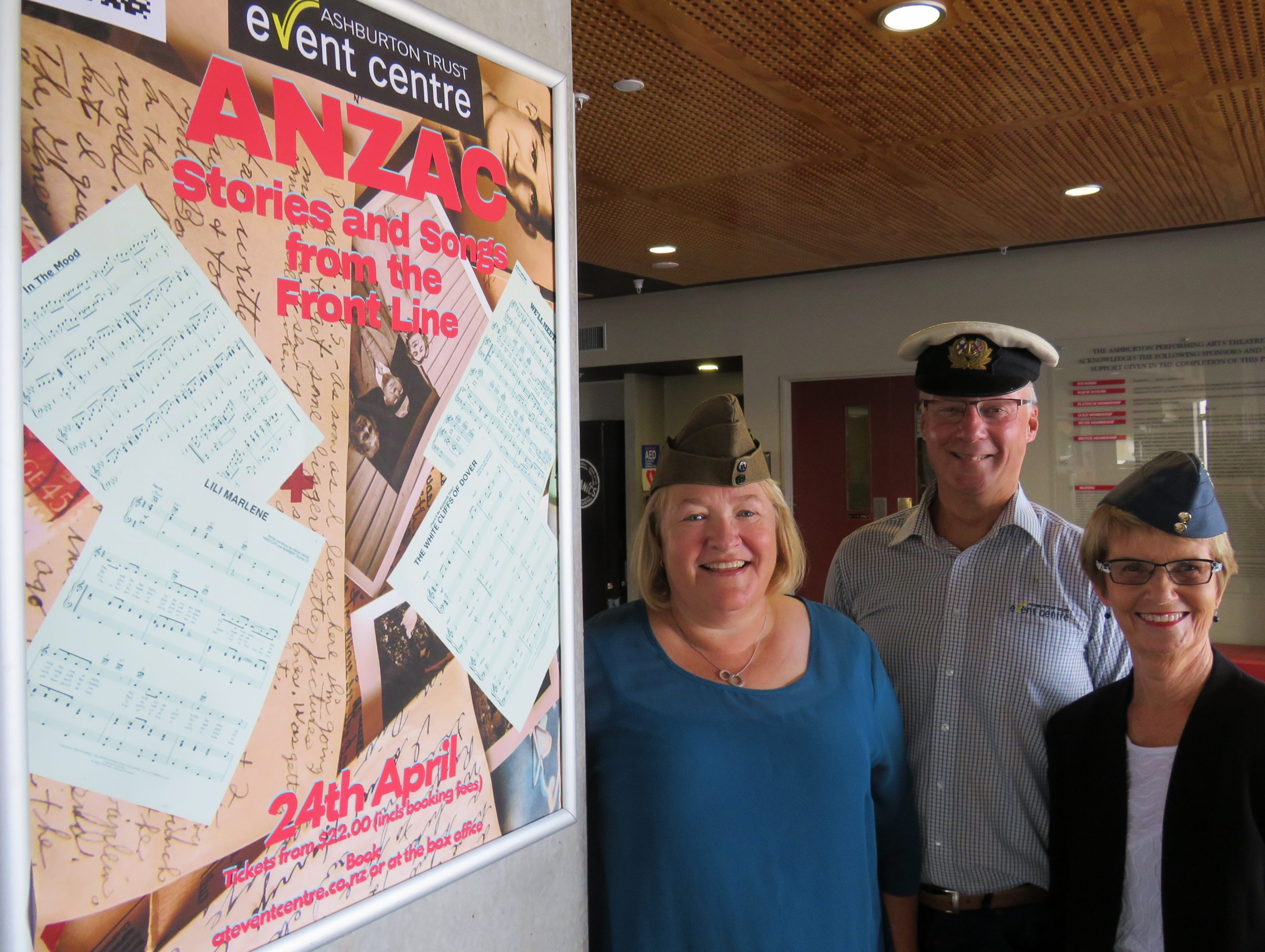 Wearing military hats and standing to attention are show compilers (from left) Sally Farr, Roger...