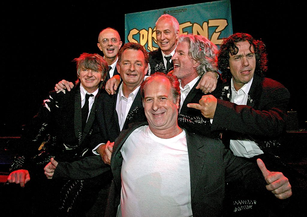 Michael Gudinski (c) poses with Split Enz during a press conference in Melbourne in February 2006...