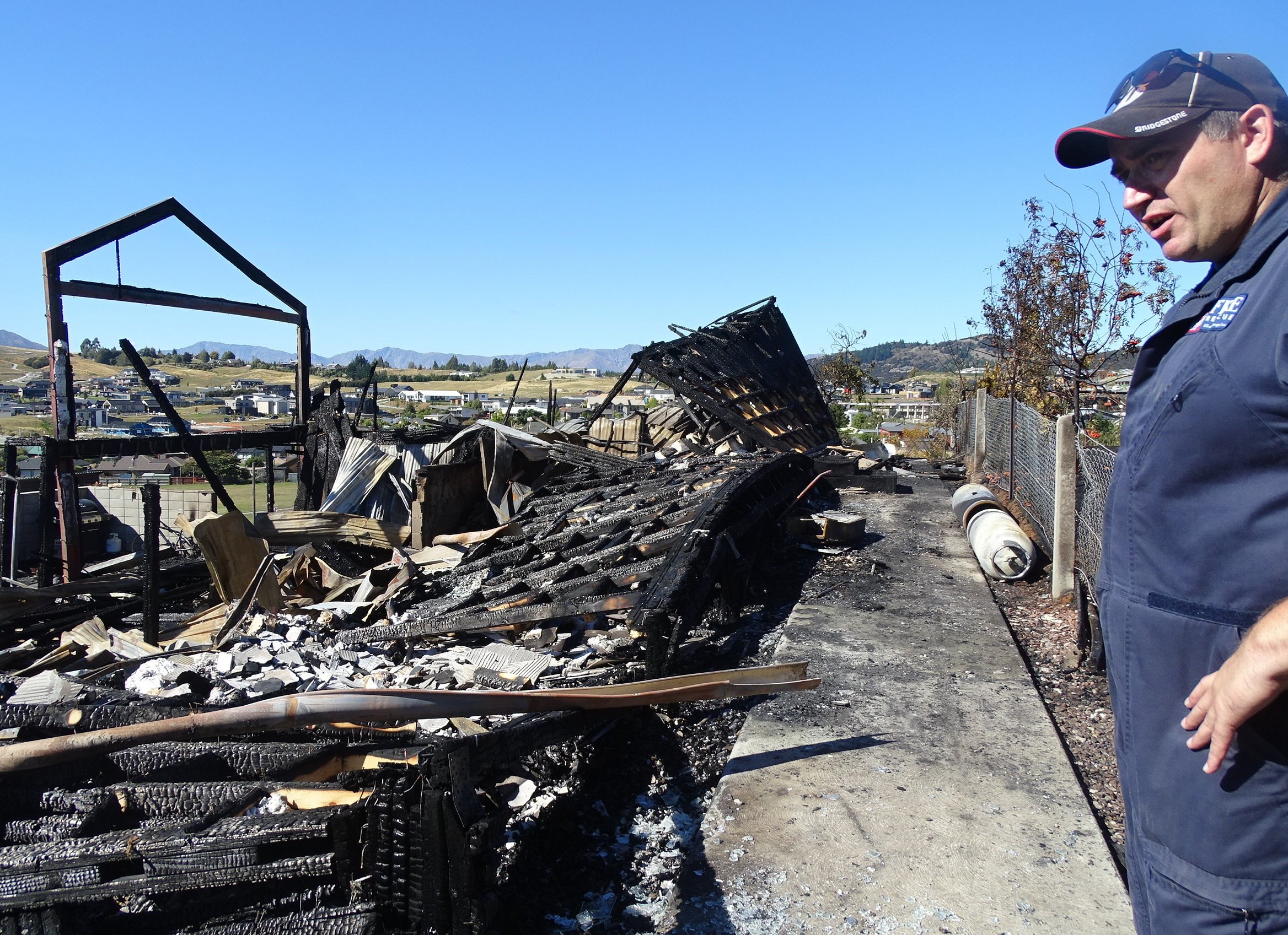 Fire investigator John Smalls examines the destroyed house. Photo: Kerrie Waterworth.