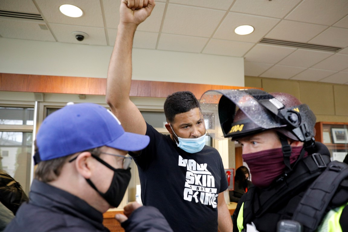 An activist confronts an officer inside the Brooklyn Center Police Department after the death of...