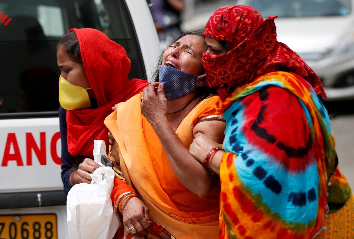 A woman is consoled outside a hospital in Ahmedabad after the death of her husband due to...