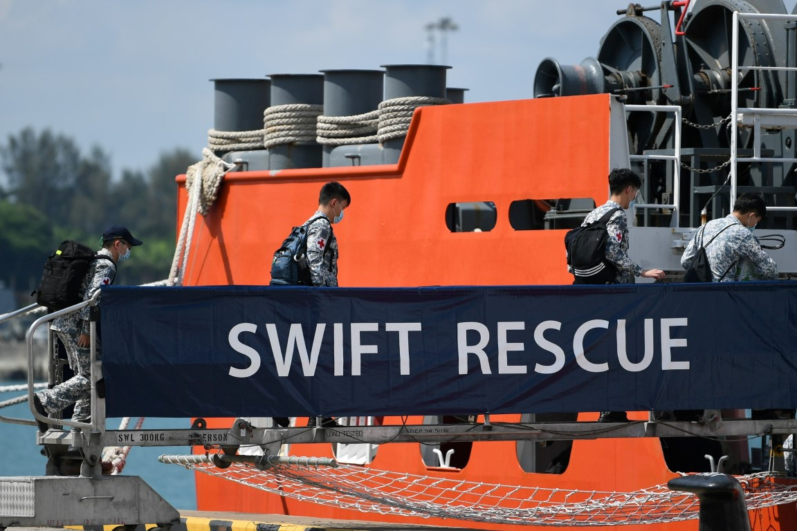 Officers board Singapore Navy's MV Swift Rescue as the search continues for Indonesia's missing...