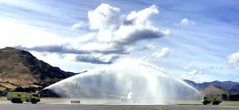 The plane makes its way under the water arch on arrival to Queenstown Airport. Photo: RNZ