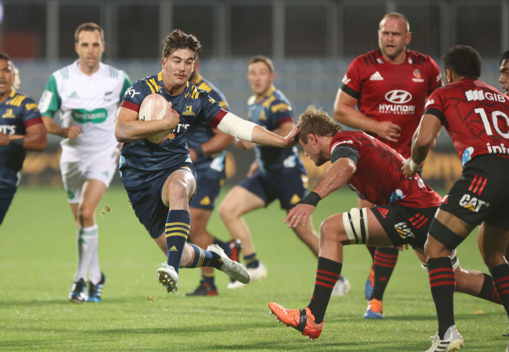 The HIghlanders' Connor Garden-Bachop fends off the Crusaders' Ethan Blackadder.  Photo: Getty