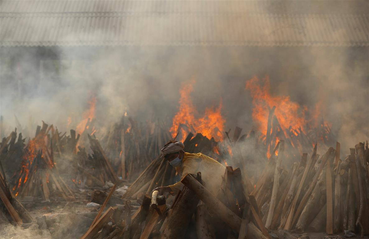 A man prepares a funeral pyre during a mass cremation of coronavirus victims at a crematorium in...
