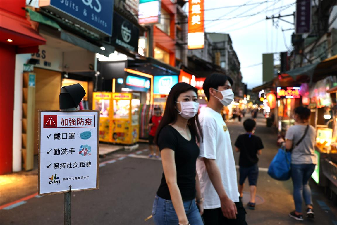 """People walk past a sign reading """"Wear protective face mask, wash your hands and keep social..."""