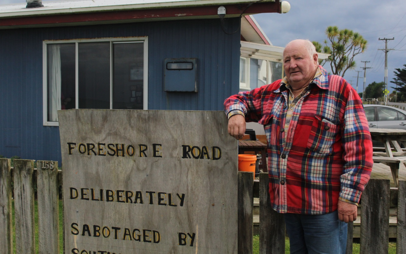 Kevin Mulqueen leans against a sign he attached to the fence of his Colac Bay home. Photo: LDR /...