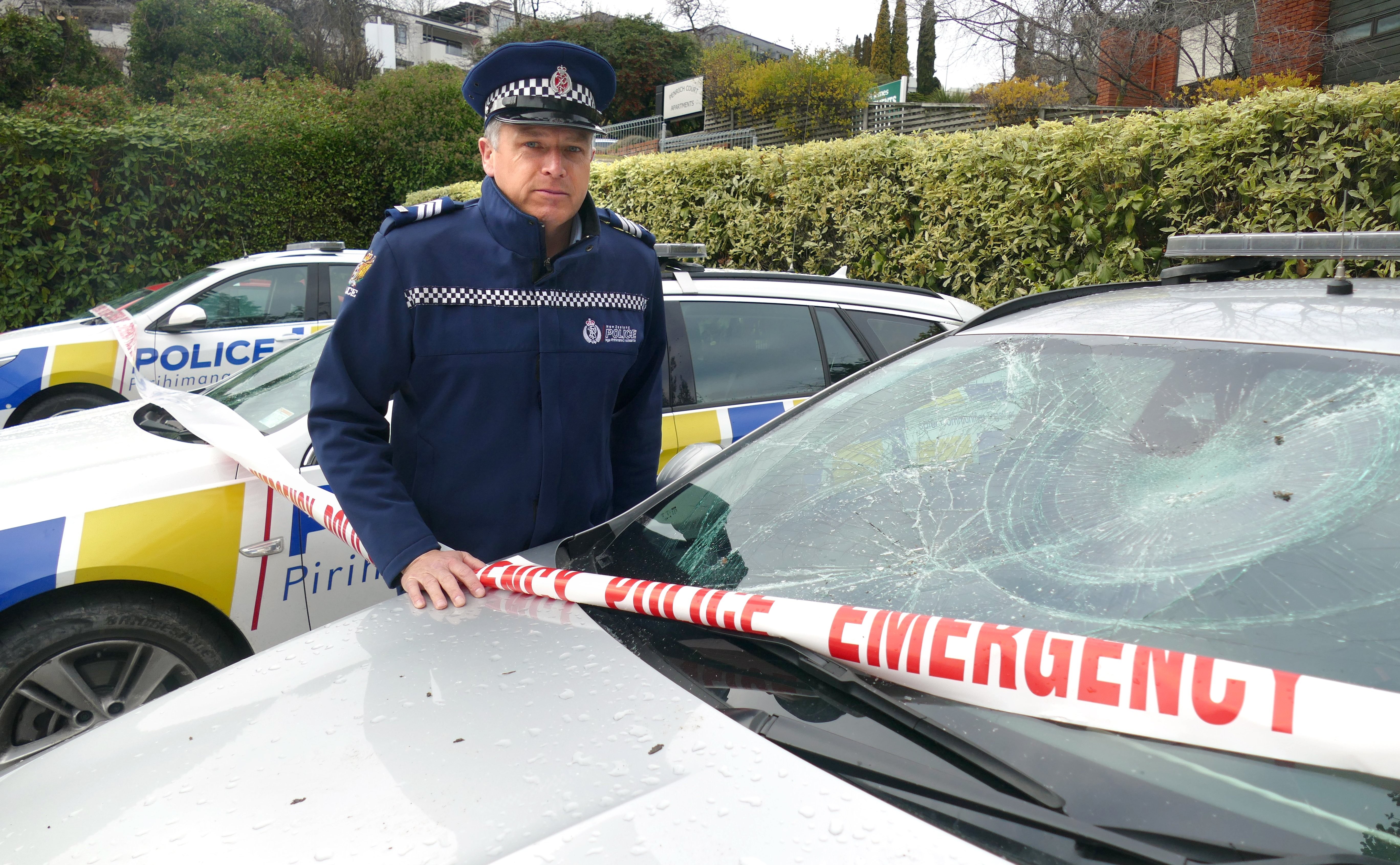 Sergeant Simon Matheson, of Queenstown, inspects some of the police cars damaged at the station...