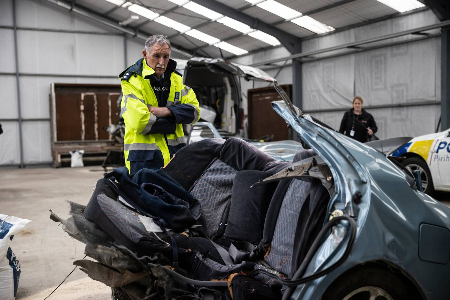 Inspector Dave Gaskin looks over the car, which was ripped in half by the impact. Photo: NZ Herald