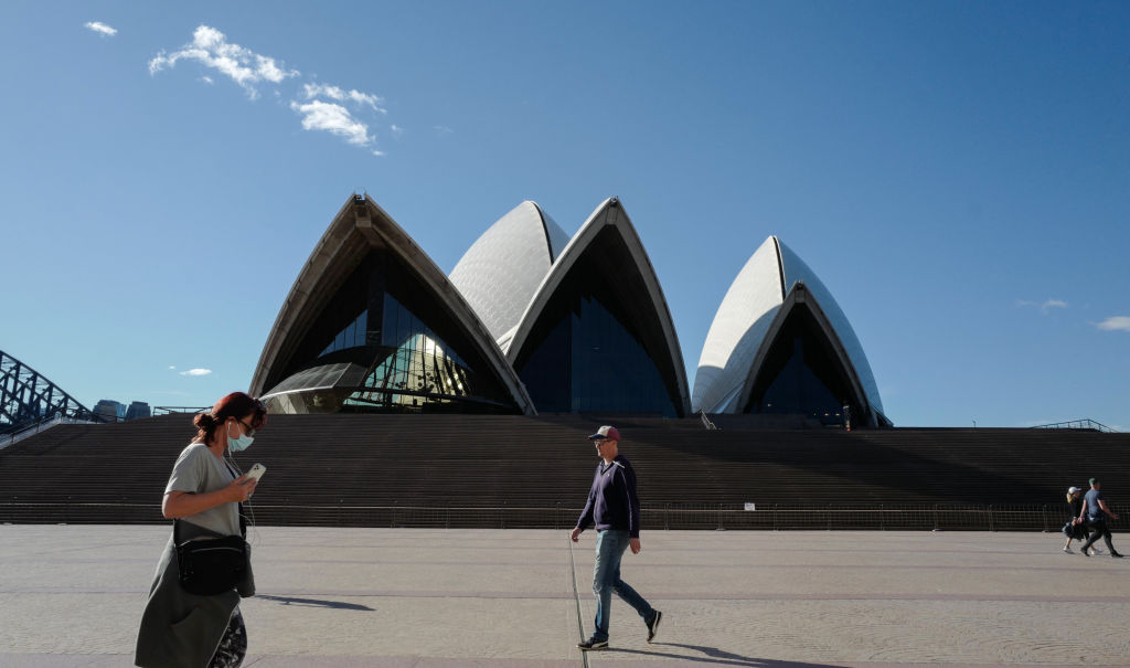 People exercise at a distance from reach other beside the forecourt of the Sydney Opera House during the city's lockdown, which is in place until at least August 28. Photo: Getty