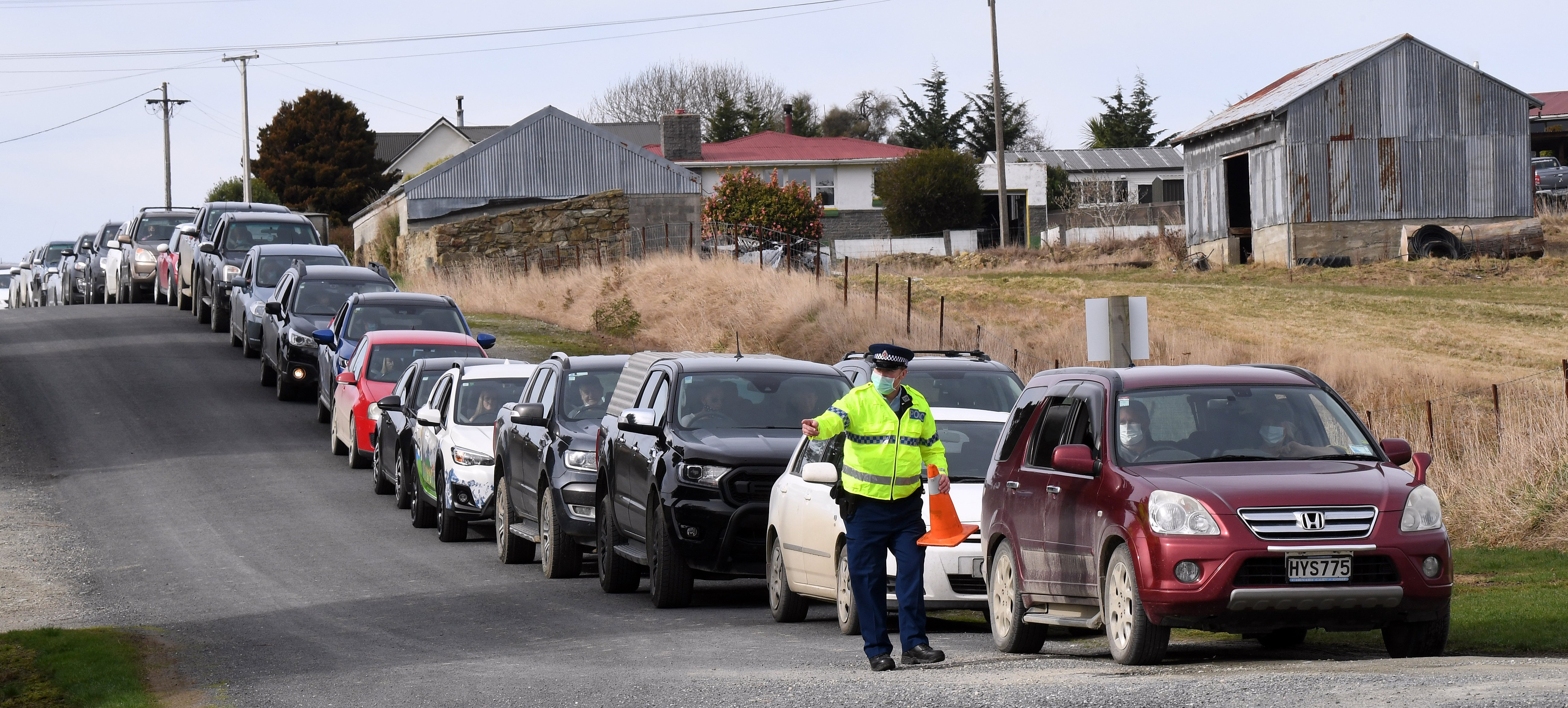 Constable Paul Alden, of Lawrence, marshals vehicles queuing at the entrance to the town's...
