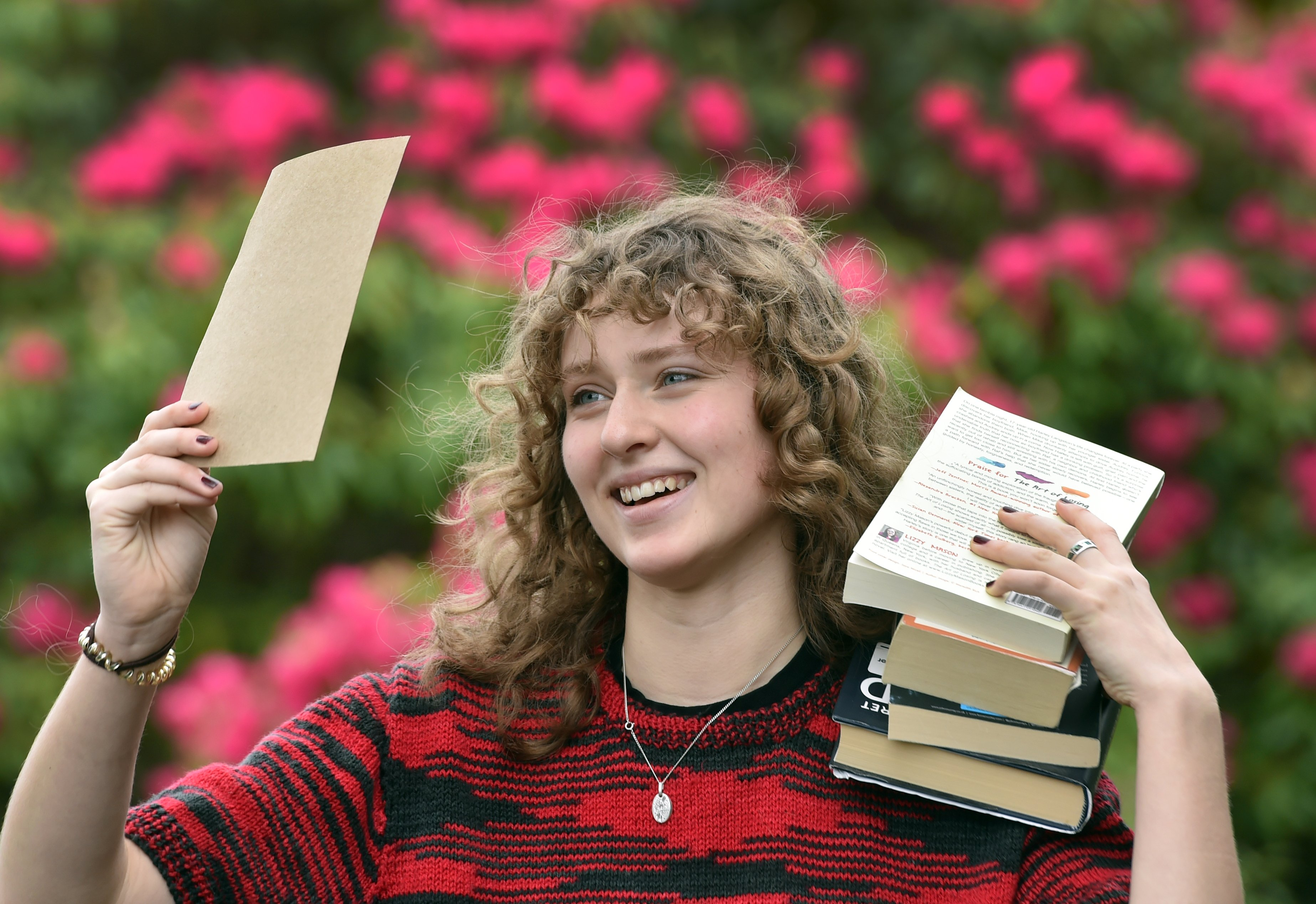 Holding up some of her work and a stack of literary influences is National Schools Poetry Award...