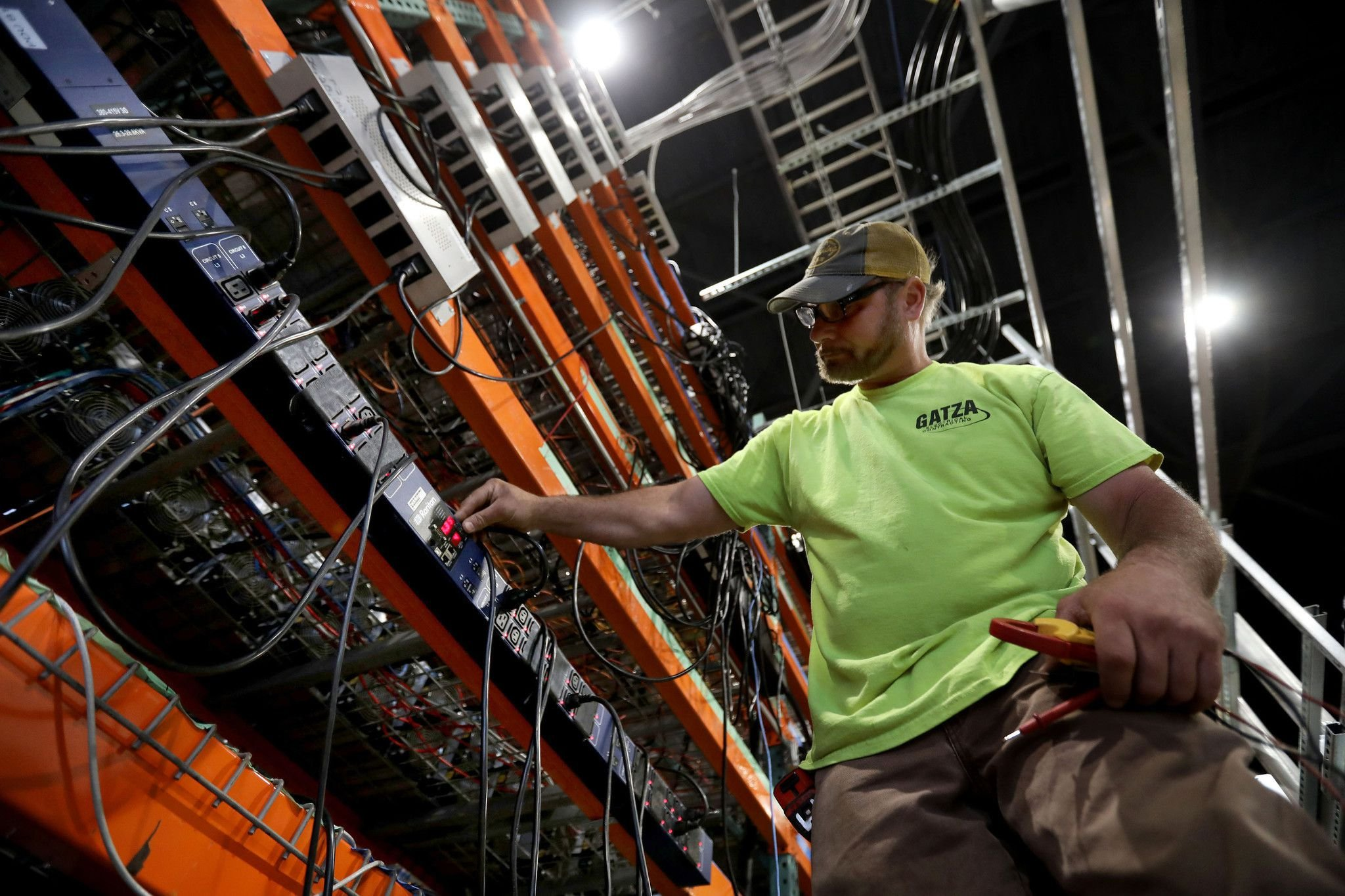 An electrician checks voltages and amperages on cryptocurrency computer mining rigs at...