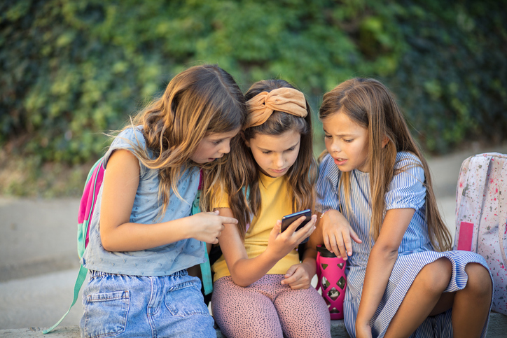 three girls looking at phone getty