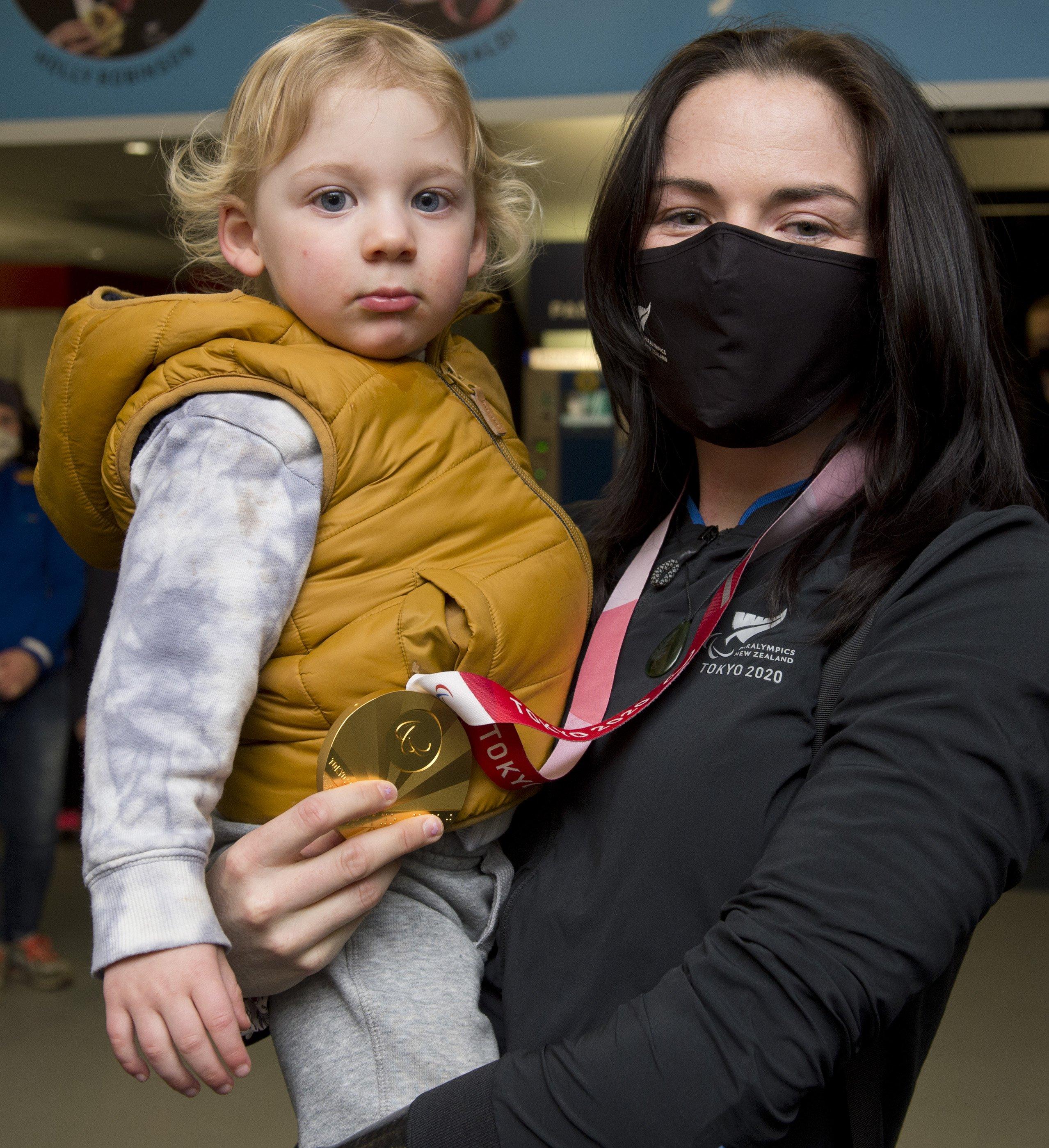 Paralympian Holly Robinson shows off her F46 javelin gold medal to godson Thomas Bates at Dunedin...