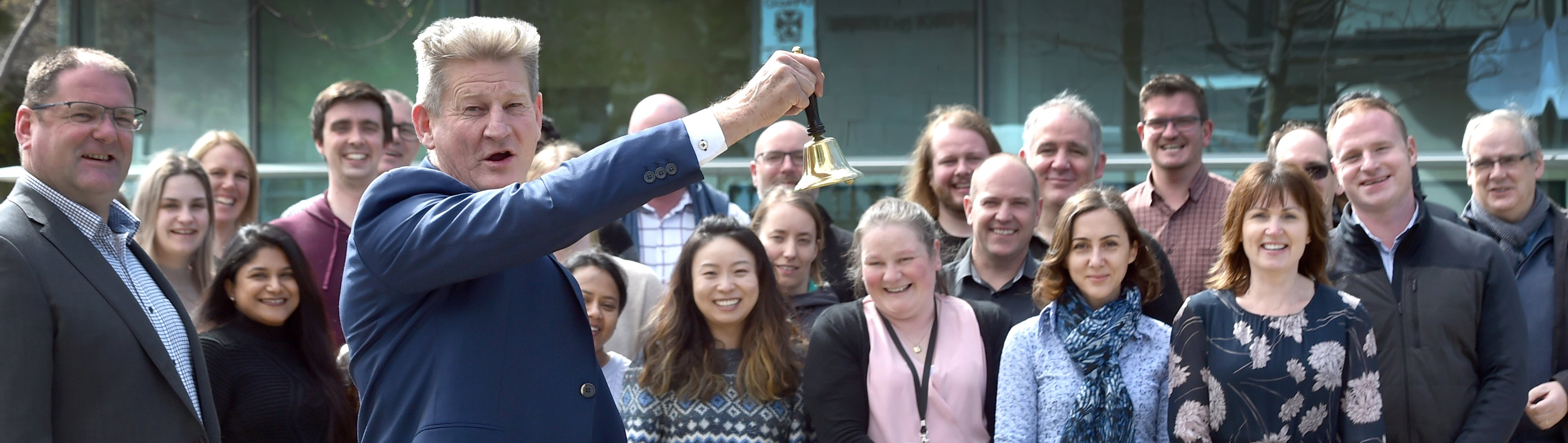 Pacific Edge chief executive David Darling rings a bell, watched by staff, in celebration of the...