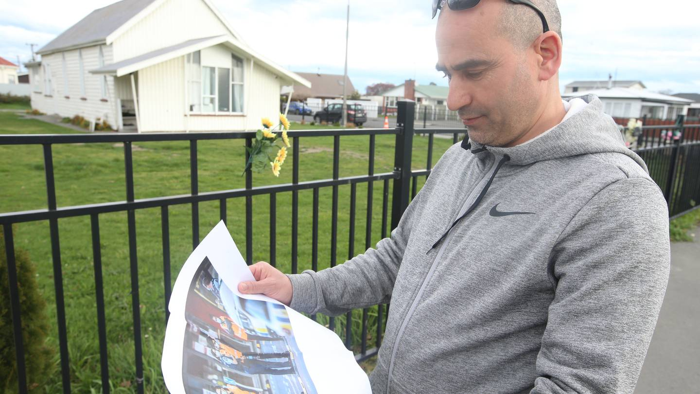 El Ouafi Aghoutan glances at a photo of the aftermath of last week's terror attack. Photo: Adam...