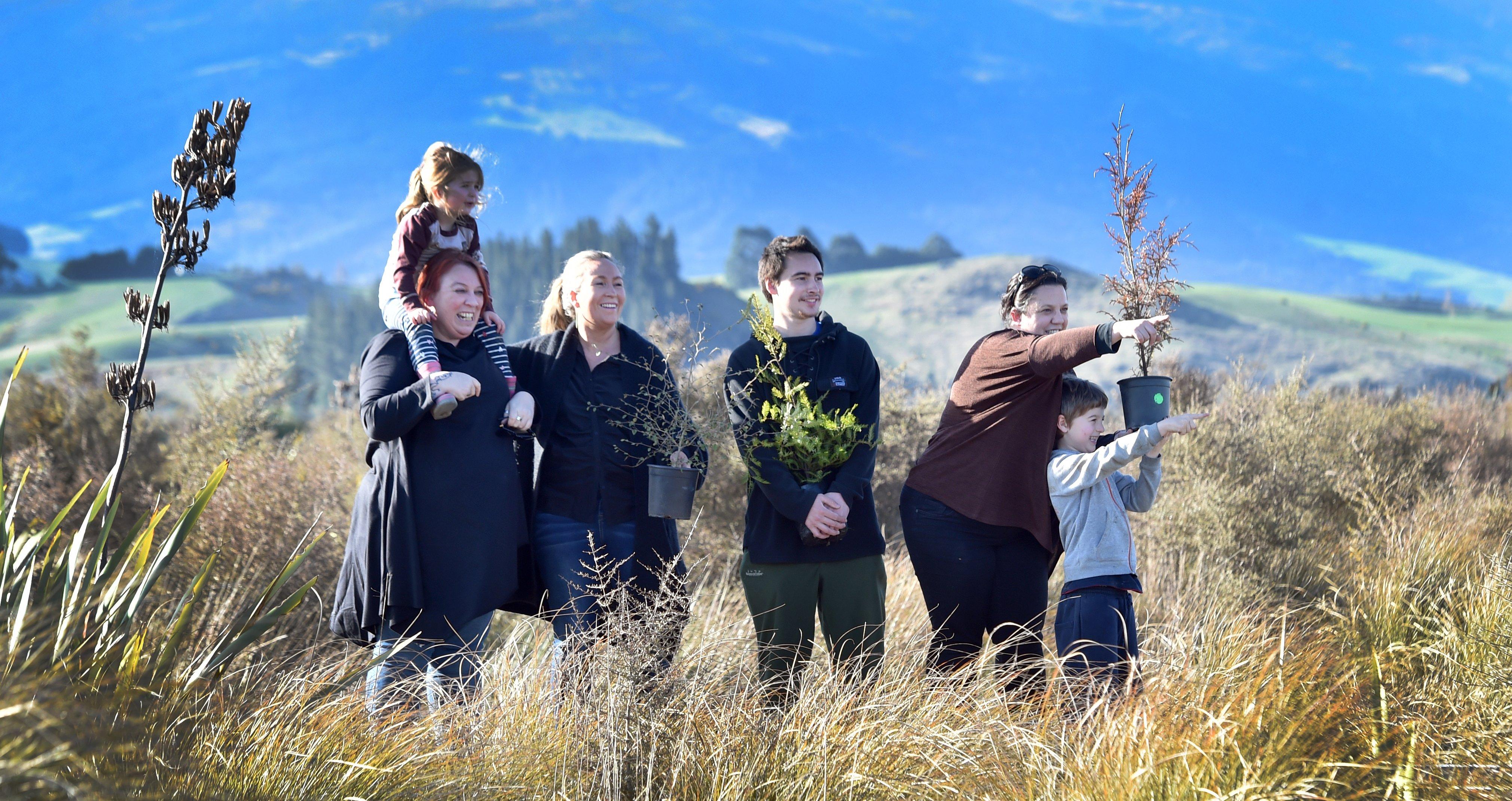 Surveying potential planting sites for native shrubs are Te Runanga o Otakou members (from left)...