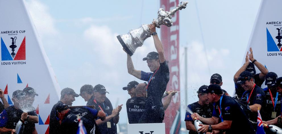 Team NZ's helmsman Peter Burling celebrates winning the America's Cup trophy. Photo: Reuters