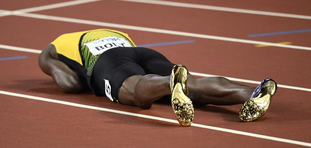 Bolt crashed on the track after suffering cramp. Photo: Reuters