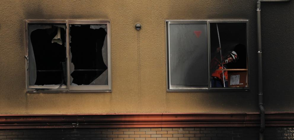 A firefighter inspects the interior of the torched Kyoto Animation building in Kyoto. Photo:...