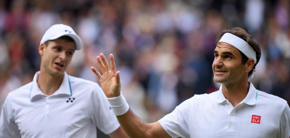Roger Federer waves to the Centre Court crowd after losing his quarterfinal match against Hubert...