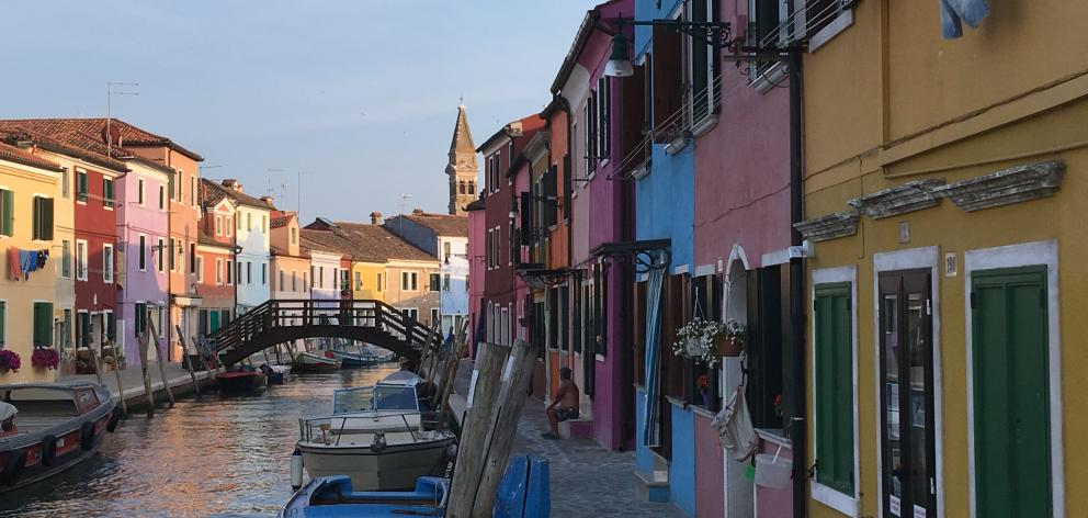 Multicoloured houses line a canal in Burano, in the Venice Lagoon.