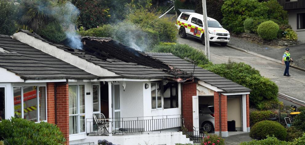 Smoke rises from the damage caused by a house fire in Challis St which left one person dead. Photo: Stephen Jaquiery