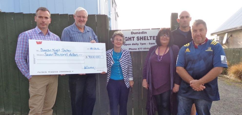 Goodman Fielder plant manager Gary Simmons (left) hands over a $7000 cheque from the firm's annual golf  tournament to Dunedin Night Shelter Trust chairman Dave Brown (second from left) and trust secretary Pat Robertson (centre),  while members of the G