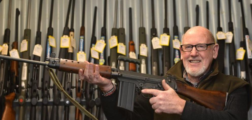 Centrefire McCarthy managing director Selwyn Shanks, holding a FN FAL L1A1 military-style semi-automatic, says cheaper weapons have helped boost firearms sales. Photo by Peter McIntosh.