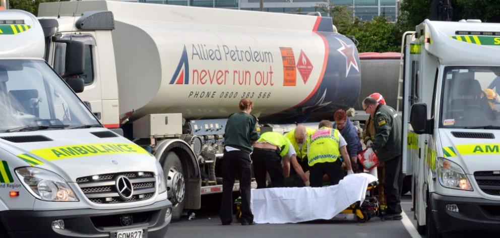 Emergency services assist a pedestrian knocked down by a petrol tanker yesterday morning.