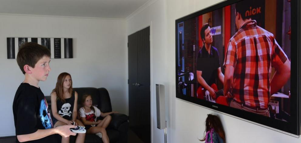 Mosgiel youngsters (from left) Anthony  (12), Latisha  (14) and Adriana (9) Mellon watch television at their home yesterday. Photo by Peter McIntosh.