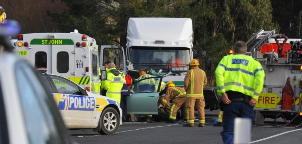 Emergency services work to free  a car driver in a critical condition after the vehicle and a truck  collided  near the intersection of State Highway 1 and Henley Rd yesterday. Photo by Craig Baxter.
